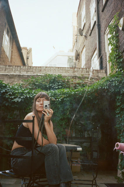 Flaneur luxury bedding partner, photographer, tastemaker Magdalena Wosinska in a courtyard looking through lens of her camera.